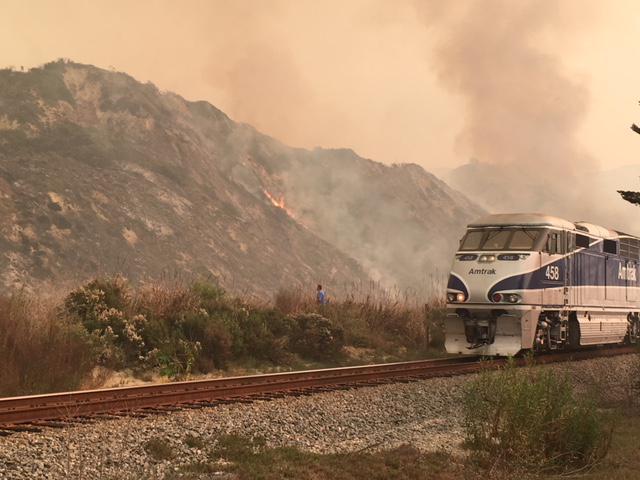 An Amtrak train heading from Santa Barbara to Ventura passe by part of Ventura County's Thomas Fire