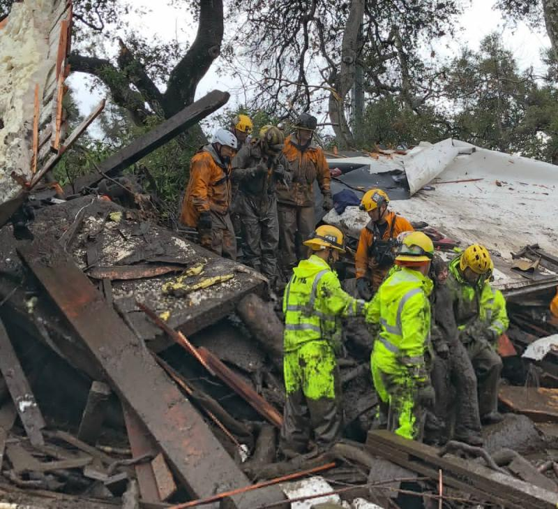 Firefighters rescue a 14 year old gril who had been trapped in the rubble of a Montecito home destroyed by flooding