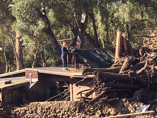 Search team members from San Bernardino County look at a house on East Valley Road in Montecito