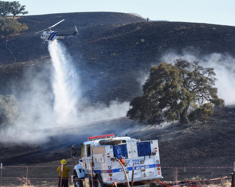 A helicopter make a water drop on a brush fire west of Buellton Friday evening