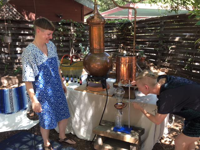 Lauren Crow and Clara Anderson with a still they use to make their natural hydrosol elixir