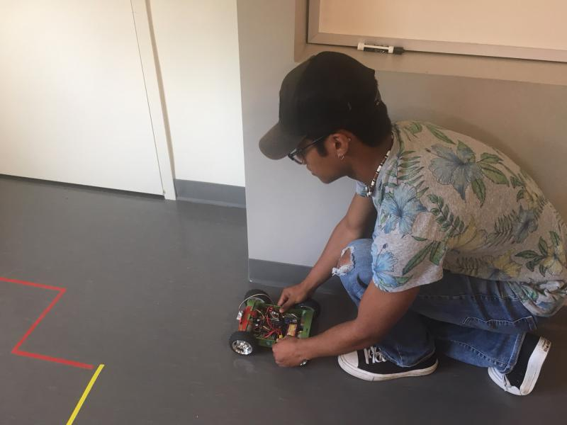A student tests out his small robot that he has programmed to move without hitting obstacles