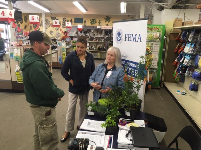 FEMA workers have set up an information booth at a Ventura nursery, to help fire, flood victims with relandscaping ideas