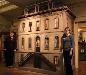 Executive director Jamie Berry and museum educator Laura Taylor next to the Coleman dollhouse, the largest object in the collection.