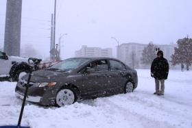 Up to Date senior producer (right) Stephen Steigman helps get show host Steve Kraske (behind wheel) unstuck and into the parking lot at KCUR.