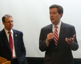 Kansas Governor Sam Brownback (r) speaking with Doug Girod (l) and other KU Medical Center officials Thursday afternoon about the importance of continued state funding to the medical center. The state House's budget proposal would cut about $11 million from the center.
