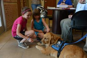 Some young girls interact with a comfort dog from Lutheran Church Charities after the tornado in Moore, Okla.