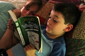 """A child reads the popular book, """"Diary of a Wimpy Kid."""""""