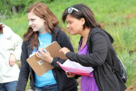 Lexicon of Sustainability fellows Erin Cochran and Elena Ingram, both Ames High School juniors, watch a photo shoot at Berry Patch Farm.