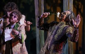 Bruce Roach, as Jaques, stops to smell the flowers in 'As You Like It.'