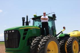 Admitting he's a boy who loves big toys, Howard Buffett stands on his John Deere tractor on his Arizona research farm.