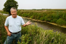 Farmer Tim Smith stands by a creek that cuts through his property near the north-central  Iowa town of Eagle Grove. He does several water quality conservation practices on his land including a bio-reactor, strip tilling and cover crops.
