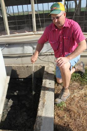 Reinart checks the depth of the foam in the manure pit.
