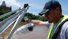 Joe Schatz, a hydrologist with the U.S. Geological Survey, prepares to take a sample of Missouri River water near Hermann, Mo.