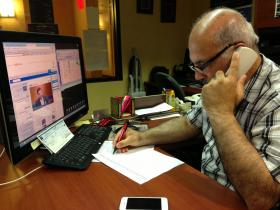 Fariz Turkmani watches news from Syria while he works in his office at the Marriott in Overland Park, Kan.