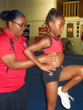 CJ Nash helps one of her students at the cheerleading gym she founded with her sister, Jamisha Miller.