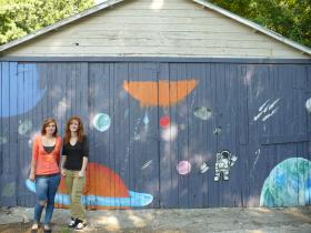 Sisters Amber Finley and Marie Abed pose in front of this outer space themed Art Squad alleyway mural.