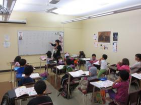 A kindergarten teacher at the Kansas City Chinese School points to characters on the white board.