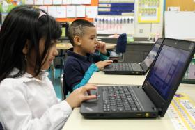 Kindergartners at James Elementary use laptops in the classroom.