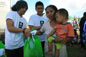A victim of typhoon Haiyan receives a hygiene kit.