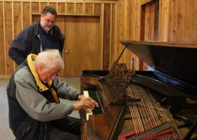 Jim Upton listens carefully, as Dr. Bruce Prince-Joseph plays the newly restored piano at the Alexander Majors House.