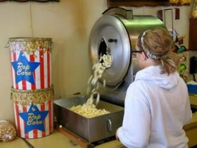 A Del's Popcorn shop employee in Decatur, Ill., starts the vintage popcorn popper. Del's relies heavily on holiday sales, but is struggling with the high price of popcorn.