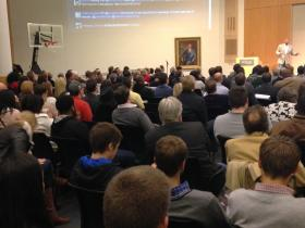 Hundreds of people often show up for 1 Million Cups. An ongoing twitter feed is projected on the wall.