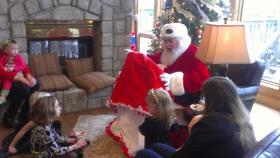 Santa Claus shows children the blanket he received from Kelly Clark and her family.