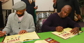 Shane Evans (left), and Taye Diggs sign copies of Chocolate Me for fans.