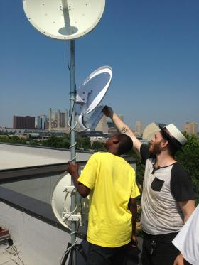 Issac Wilder (right) and assistant add a dish to a tower at Posada del Sol to send bandwidth over to the 18th and Vine district.