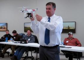 Agriculture consultant Chad Colby shows a room of Midwest farmers how GPS can control a high-definition camera attached to a UAV.