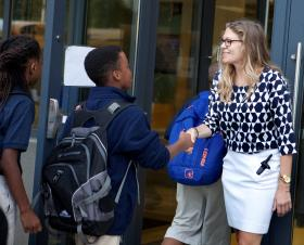 Hannah Lofthus greets Kauffman School students on the first day of classes in August, 2013.