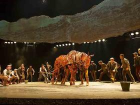 Joey the War Horse, in the play by the same name, surrounded by villagers.