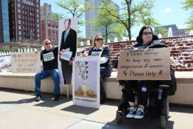 "Protestors, like disabled veteran Sara Campbell (at right), held signs across the street from ALEC's meeting in Kansas City, Mo. Chuck and Tina Tribble (left, and center) planned to stay until the meeting ""broke for dinner."""