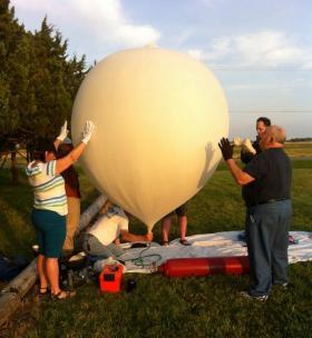 Volunteers keep the balloon steady as Paul Verhage prepares for launch.