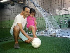 David dos Santos is teaching his three-year-old daughter Ariana the best of Brazilian and American soccer.