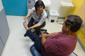 Jessie Yuan, physician at the Eisner Pediatric and Family Health Center in Los Angeles, treats diabetic patient Oscar Gonzales. Gonzalez was unaware he had been switched to Medi-Cal until Yuan informed him about the change.