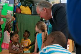 Missouri Gov. Jay Nixon speaks to a student at Operation Breakthrough, a Kansas City day care center, before signing legislation tightening the rules for child care providers.