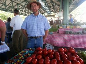 Gerry Newman of Providence Farms shows off his tomatoes at the Overland Park Farmer's Market.