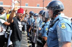 Protesters are greeted by a line of Missouri State Police during a protest march in Ferguson, Missouri on August 11, 2014.