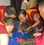 Monks from the Kharnang monastery in Tibet begin to create the sand mandala