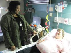 Brenda Bush, left, a Saint Luke's Hospital  patient advocate visits Dawn Brock who is on bed rest.