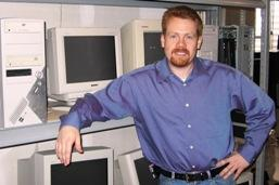 Joshua Montgomery, founder of Community Wireless Communications, leans against some computers at his office in Lawrence, Kan.