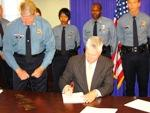Mo.Lt. Gov. Peter Kinder signs KC police bills into  law. Police Chief  Jas. Corwin  (L).