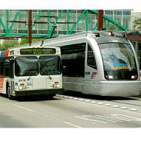 A light rail train like those envisioned in Kansas City beside a contemporary bus.