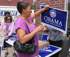 Earlene Franks of Kansas City takes a  yard sign at the local Obama office opening. She says she'd like to volunteer her time as well.