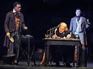 Left to right: Walter Coppage, as Bob Cratchit; Gary Neal Johnson, as Scrooge; and Robert Gibby Brand, as Charles Dickens.