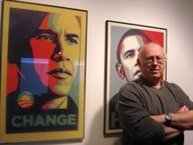 KCAI professor Hal Wert stands in front of two posters by artist Shepard Fairey