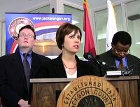 Cathy Jolly tells reporters about the jail plan as County Executive Mike Sanders and City Manager Wayne Cauthen listen.