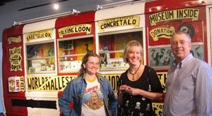 "Artist Erika Nelson of Lucas, Kansas, co-curator Kelly Ludwig, and Michael Murphy, in front of Nelson's van full of tiny sculptures based on ""World's Largest"" roadside attractions."